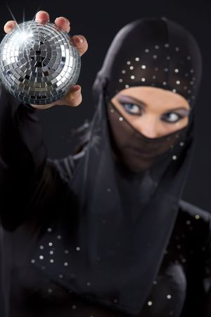 party dancer in ninja dress with disco ball (focus on hand) photo