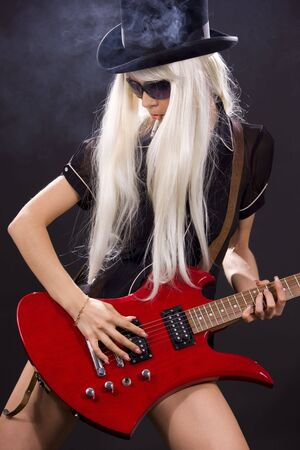 woman in top hat with red electric guitar and cigarette photo