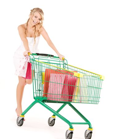 happy woman with shopping cart over white photo
