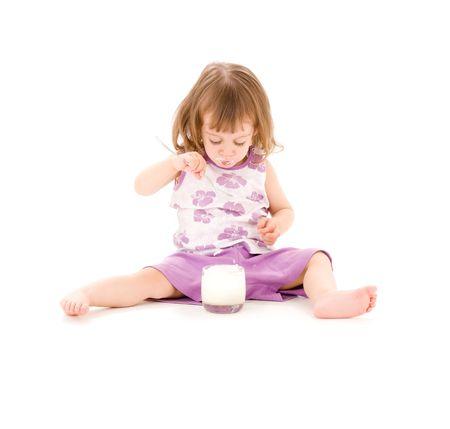ni�a comiendo: imagen de ni�a comiendo yogur sobre blanco Foto de archivo