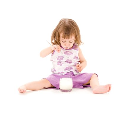 over eating: picture of little girl eating yogurt over white Stock Photo