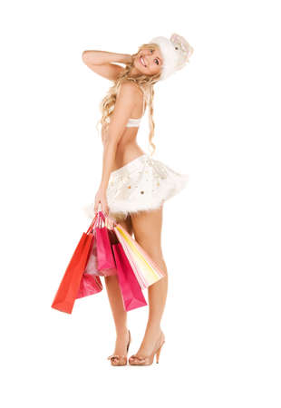 cheerful santa helper with shopping bags over white photo