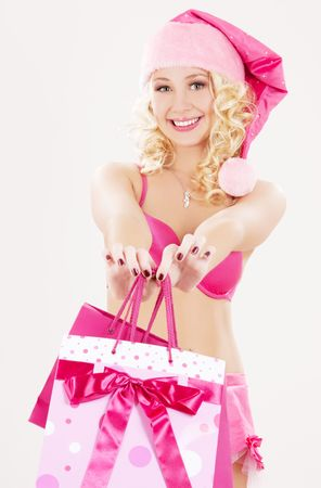 cheerful santa helper with pink shopping bags photo