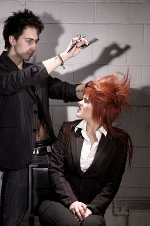 man haircut: dark picture of unhappy redhead girl and barber Stock Photo