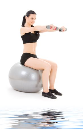 lovely fitness instructor with dumbbells on pilates ball photo
