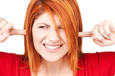 picture of unhappy redhead woman with fingers in ears photo