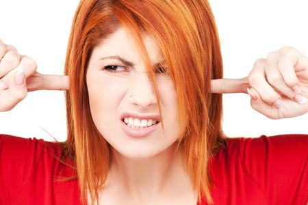 picture of unhappy redhead woman with fingers in ears Stock Photo - 6023902