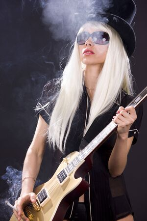 babe: woman in top hat with golden electric guitar and cigarette Stock Photo