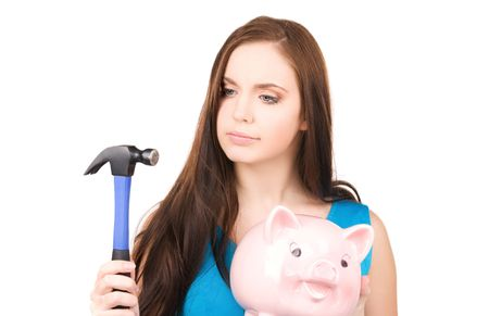 lovely teenage girl with piggy bank and hammer photo