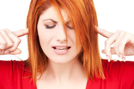 picture of unhappy redhead woman with fingers in ears Stock Photo - 6155798