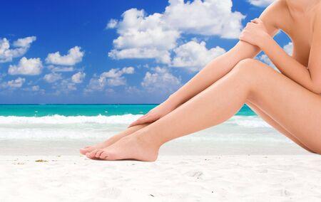 piernas de la mujer desnuda saludable sobre fondo de playa tropical