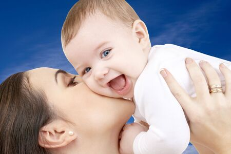 picture of happy mother with baby boy over blue sky photo
