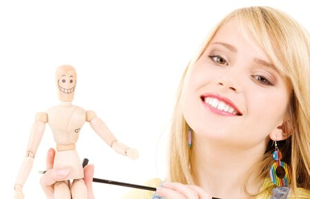 happy teenage girl with wooden model dummy over white photo