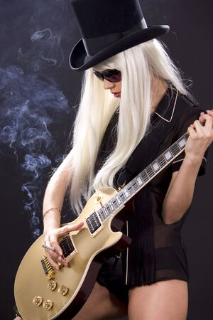 woman in top hat with golden electric guitar and cigarette photo