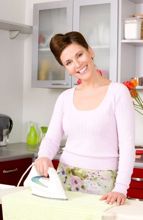 household work: picture of ironing woman in the kitchen Stock Photo