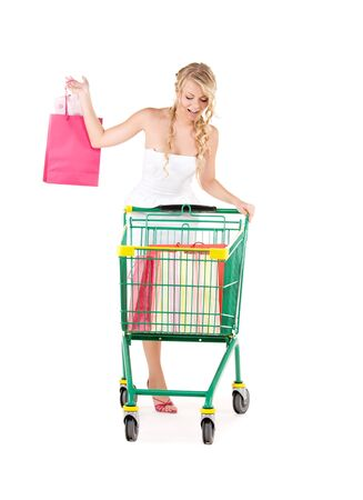 happy woman with shopping bags and cart over white Stock Photo - 6525721