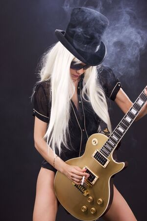 heavy metal: woman in top hat with golden electric guitar and cigarette Stock Photo