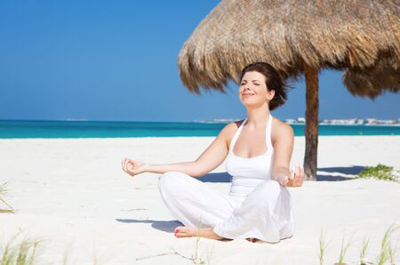 meditation of happy woman in lotus pose on the beach Stock Photo - 6663725