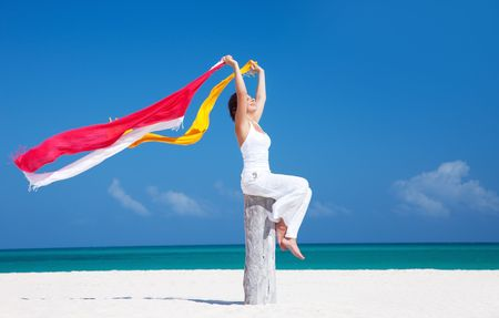 happy woman with colorful sarongs on the beach photo