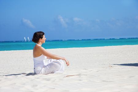poise: meditation of happy woman in lotus pose on the beach