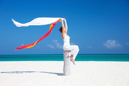 happy woman with colorful sarongs on the beach Stock Photo