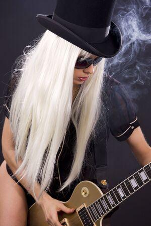guitarra sexy: mujer en top hat con oro de guitarra el�ctrica Foto de archivo