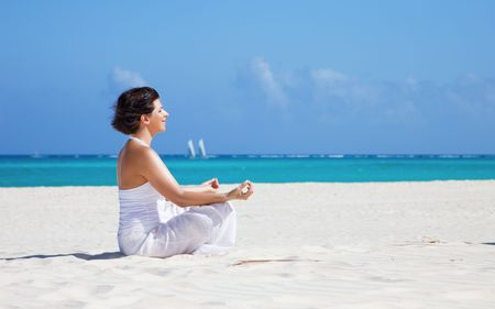meditation of happy woman in lotus pose on the beach photo