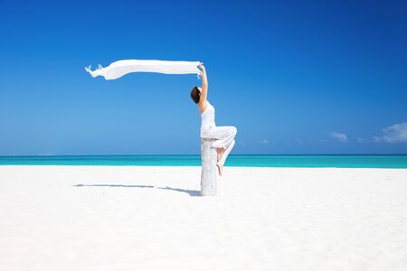 happy woman with white sarong on the beach photo