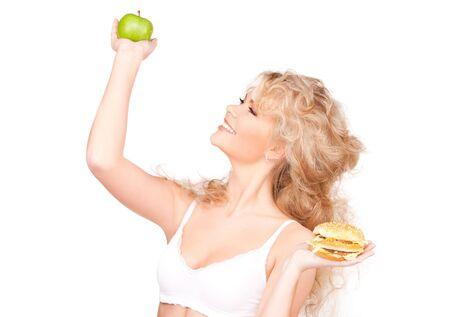 young beautiful woman choosing between burger and apple photo