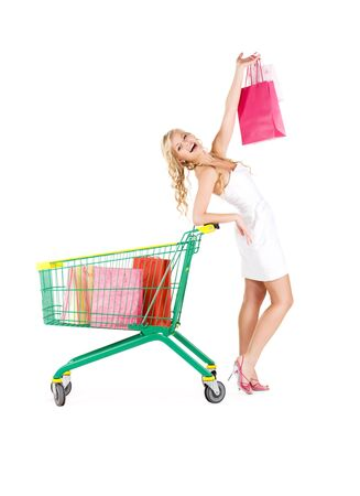 happy woman with shopping bags and cart over white photo