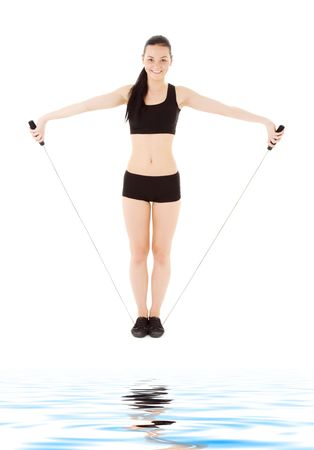 lovely fitness instructor with jump rope over white photo