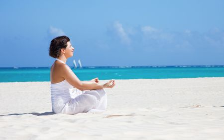 meditation of happy woman in lotus pose on the beach Stock Photo - 6806207