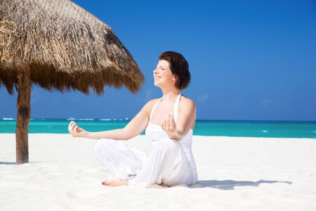 meditation of happy woman in lotus pose on the beach Stock Photo - 6806286