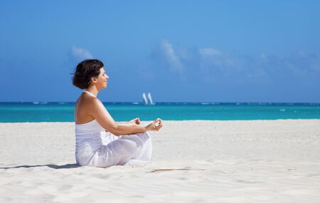 meditation of happy woman in lotus pose on the beach Stock Photo - 6861557