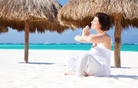 meditation of happy woman in lotus pose on the beach Stock Photo - 6862086