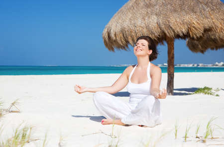 meditation of happy woman in lotus pose on the beach Stock Photo - 6945538