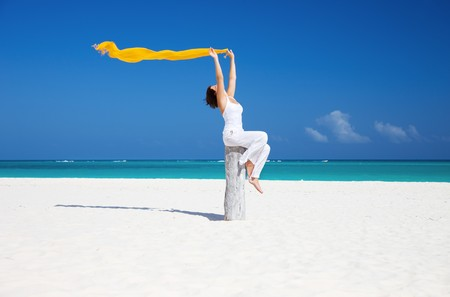 happy woman with yellow sarong on the beach photo