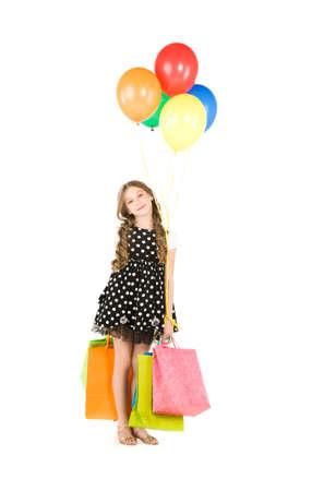 ni�os de compras: ni�a feliz con bolsas de compra y globos sobre blanco  Foto de archivo