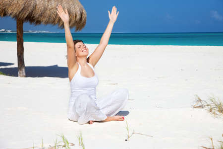 meditation of happy woman in lotus pose on the beach Stock Photo - 7010437