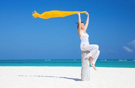 mujer feliz con sarong amarillo en la playa Foto de archivo - 7010475