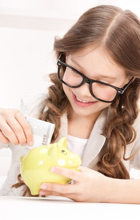 picture of little girl with piggy bank and money Stock Photo - 7372764