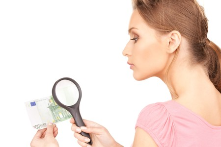 spurious: lovely woman with magnifying glass and money