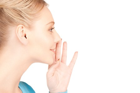 tattle: bright picture of young woman whispering gossip Stock Photo