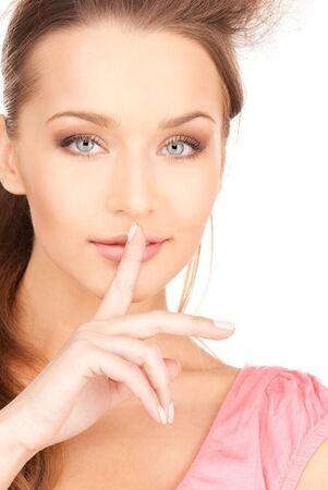quiet adult: immagine luminosa di una giovane donna con il dito sulle labbra