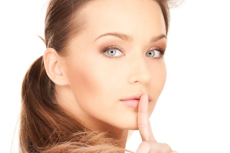 bright picture of young woman with finger on lips Stock Photo - 7595177