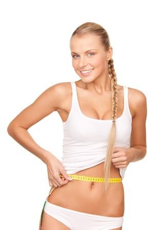 cintura perfecta: joven y bella mujer con cinta de medida sobre blanco  Foto de archivo