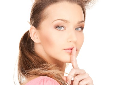 quiet adult: immagine luminosa di una giovane donna con il dito sulle labbra Archivio Fotografico