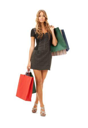 mujer encantadora con bolsas de compra sobre blanco  Foto de archivo