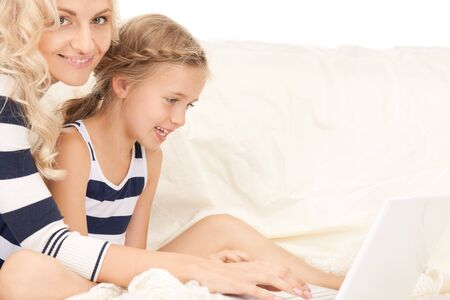 bright picture of happy mother and child with laptop computer (focus on girl)  photo