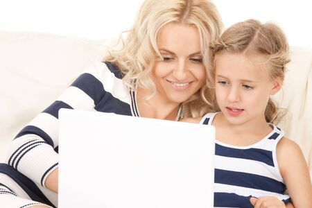 bright picture of happy mother and child with laptop computer Stock Photo - 7956897